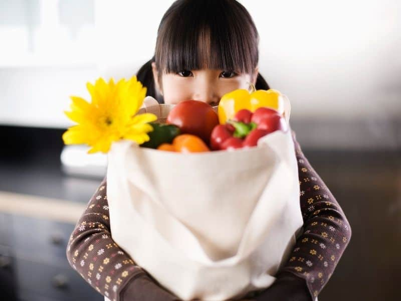 photo of kid with bag of produce