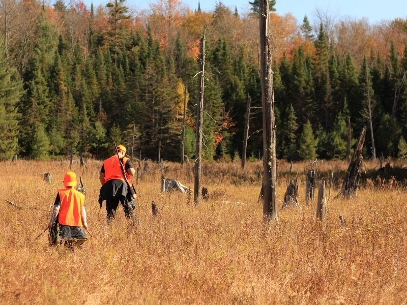 phot of two hunters walking in woods